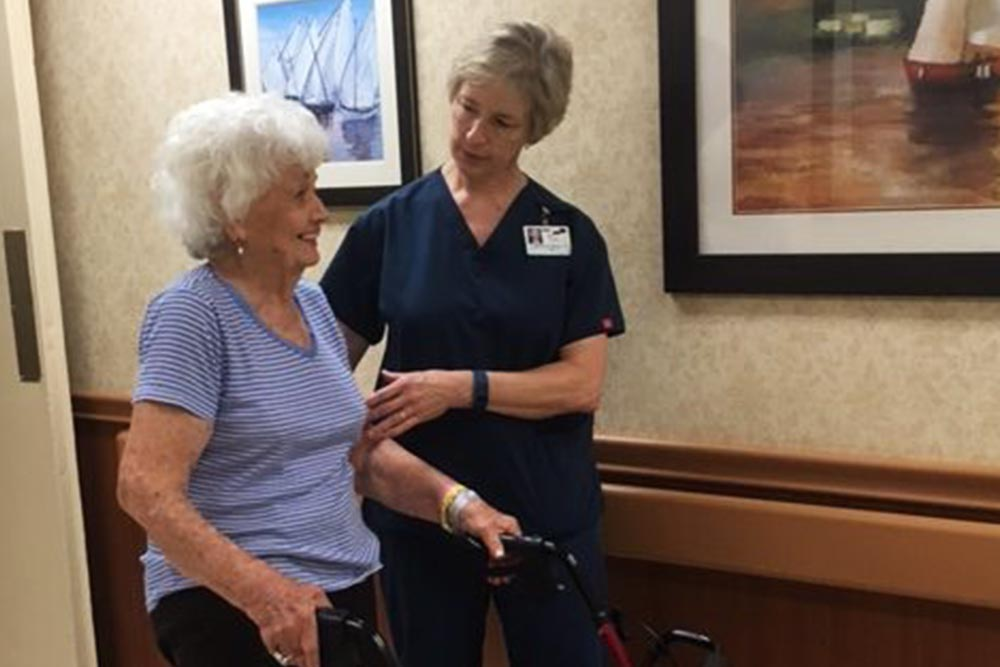 Young woman nurse helping a senior woman with a walker in the hallway.