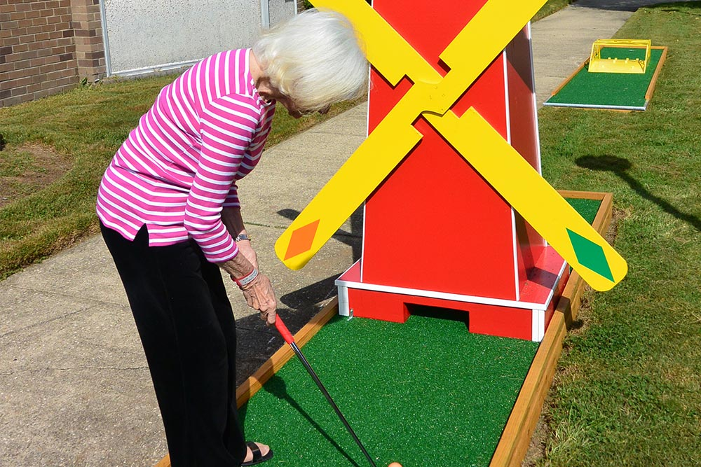 Senior woman playing mini golf on a windmill course.